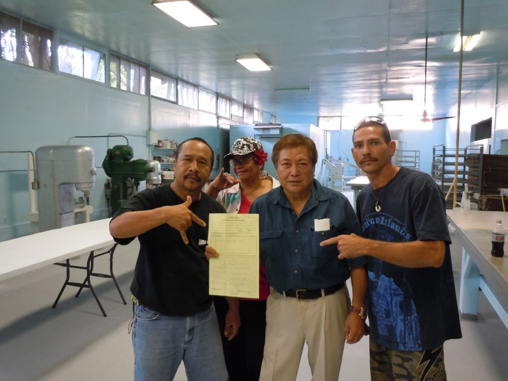 Bakery owner George Kanemitsu, second from right, holds the reinstated permit, accompanied by community members and volunteer contractors. Photo by Catherine Cluett