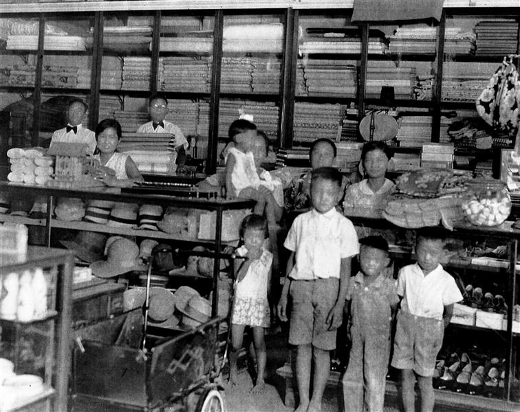 Inside Misakis in its original building, showing hats, cloth, shoes and other items for sale. Back row left to right: Friend and store clerk Masato Yoshiyoka, sales clerk Margaret Matsumura, Masataro Misaki, Uta Misaki (seated) holding daughter Irene, friend Mrs. Nishiyama, Clara (Misaki); front row Misaki children Eileen, Richard, Tadashi and Mike. Photo courtesy Irene Iwane.